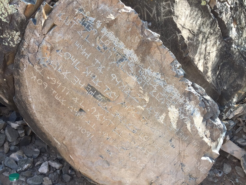 The scratching at the top of the stone is due to vandalism, this is not a protected site.